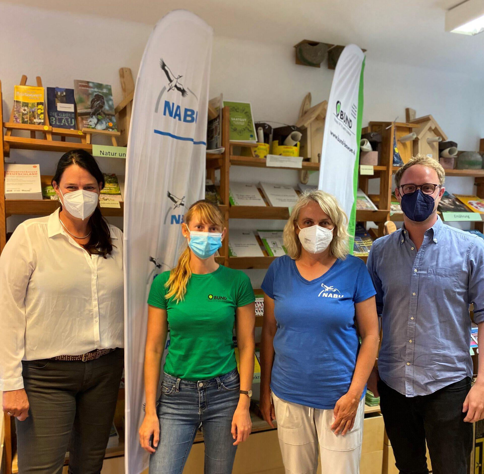 Marcel Emmerich, Dr. Anja Reinalter, Jana Slave (BUND) und Sabine Brandt (NABU) posieren für ein Gruppenfoto vor den Fahnen von NABU und BUND.