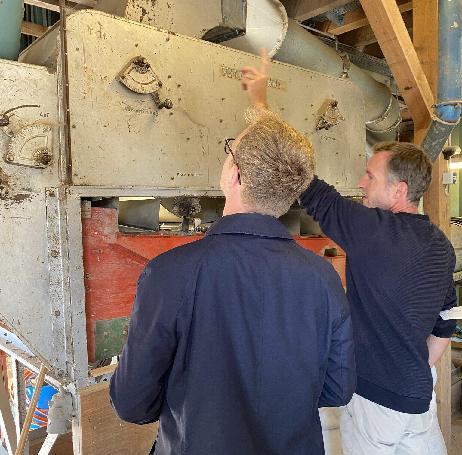 Marcel Emmerich und Lutz Mammel stehen vor einer Sortiermaschine für Feld-Früchte.