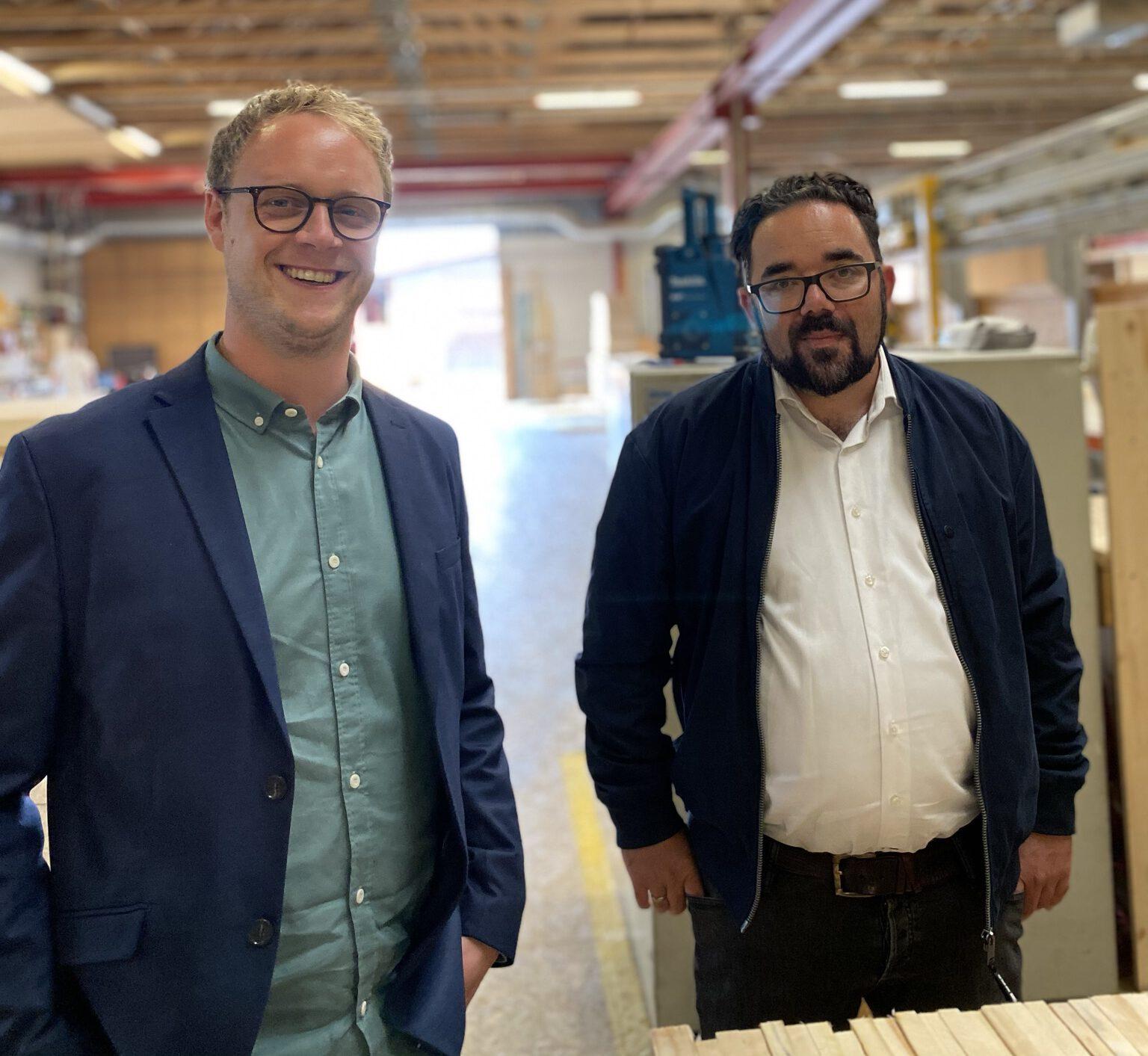 Marcel Emmerich und Christian Kühn stehen in einer Produktionshalle für Holzbauelemente.