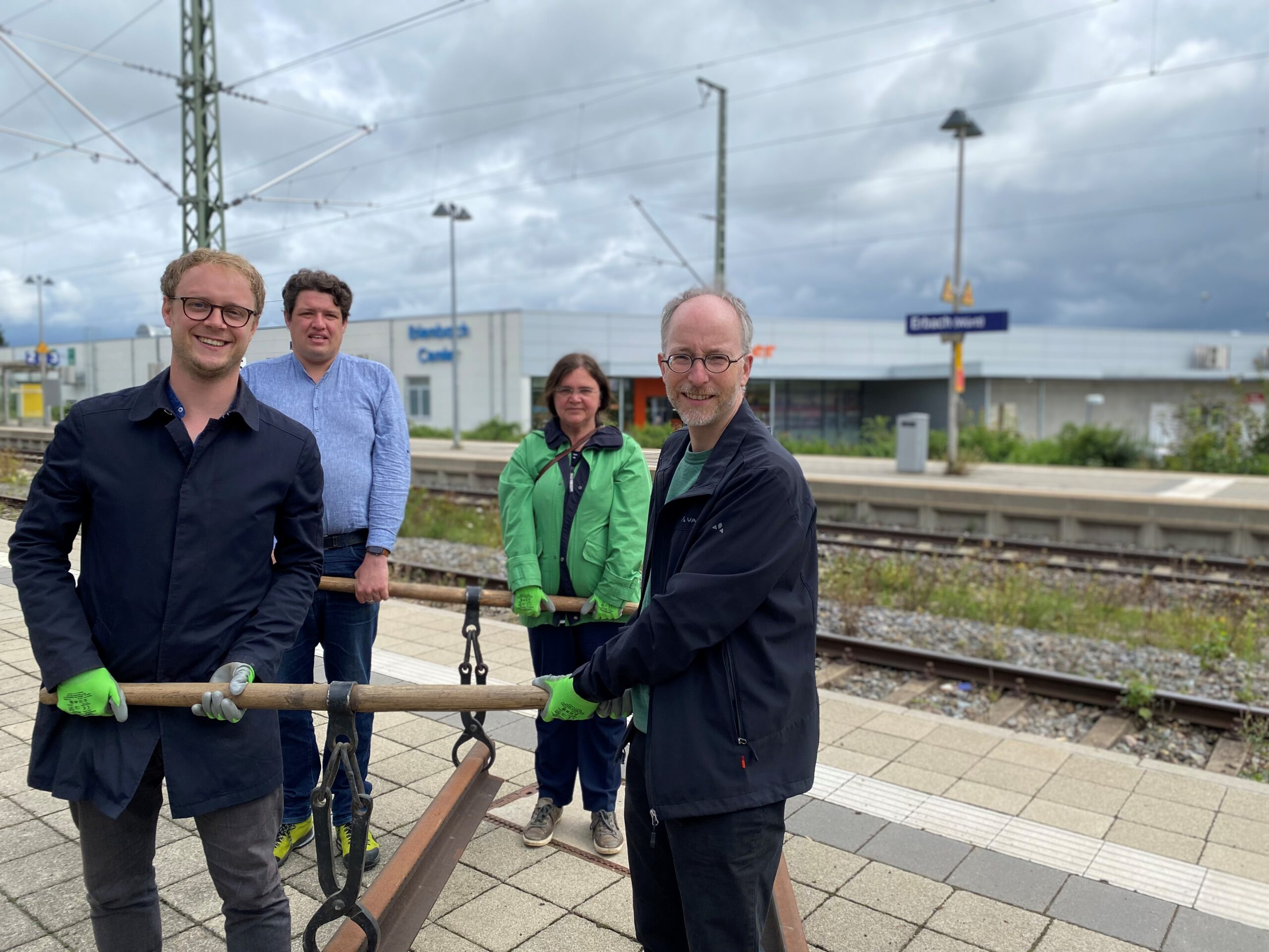 Marcel Emmerich, Matthias Gastel, Michael Joukov-Schwelling und Mona Buchenscheit heben am Bahnhof Erbach ein Schienenstück an.