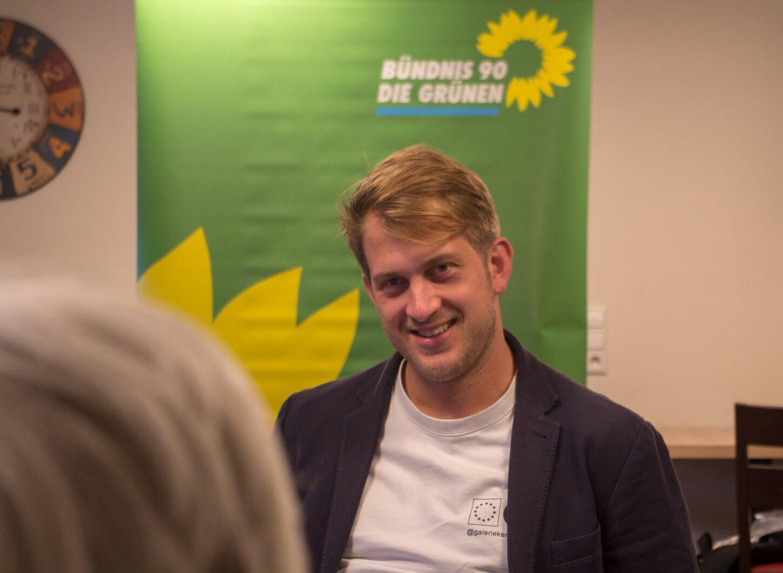 Michael Bloss im Gespräch mit einer Bürgerin. Im Hintergrund ist ein Aufsteller der Grünen zu sehen.